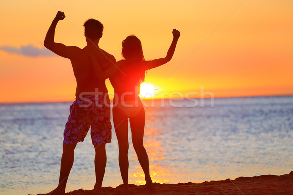 Sporty fitness couple cheering at beach sunset Stock photo © Maridav