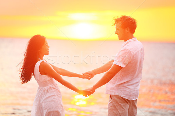 Stock photo: Romantic couple lovers holding hands, beach sunset