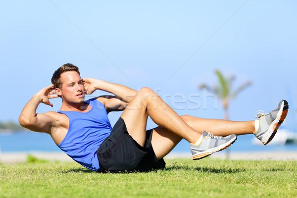 Sit ups - fitness man exercising sit up outside Stock photo © Maridav