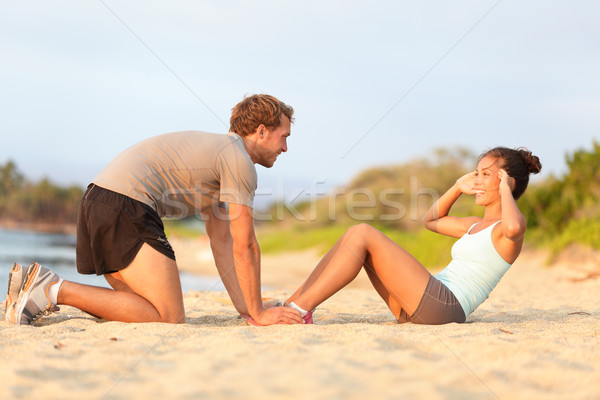 Fitness woman training situp crunches with trainer Stock photo © Maridav