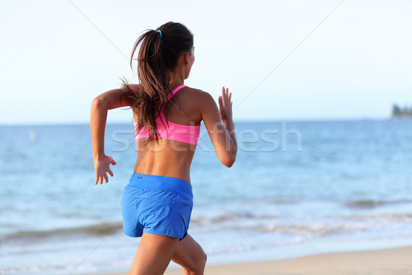 Rear View Of Determined Woman Jogging On Beach Stock photo © Maridav