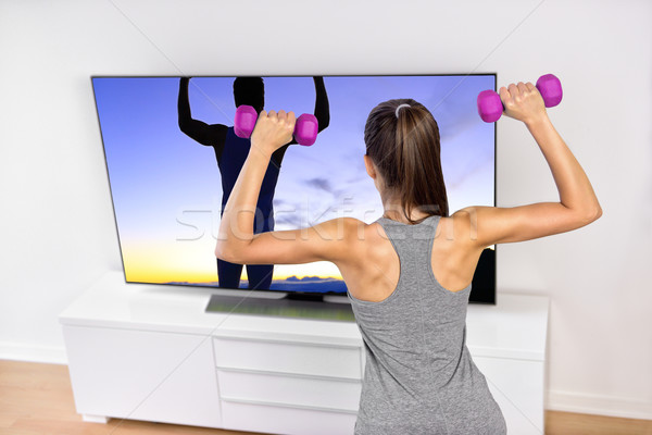 Home fitness woman strength training watching TV Stock photo © Maridav