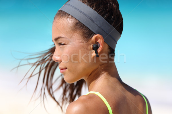 Wireless earbuds woman listening to music on beach Stock photo © Maridav