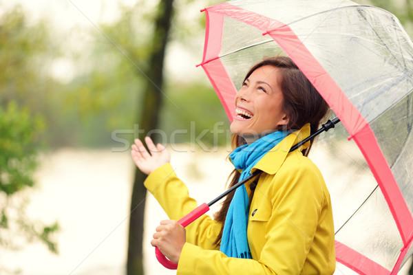 Woman happy with umbrella under the rain Stock photo © Maridav