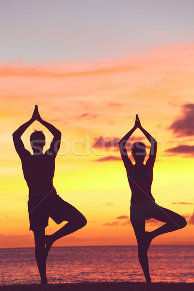 Yoga couple training in sunset in tree pose Stock photo © Maridav