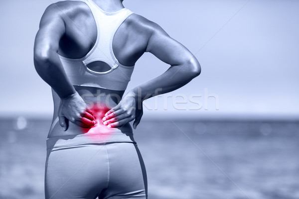 Back pain. Athletic running woman with back injury Stock photo © Maridav