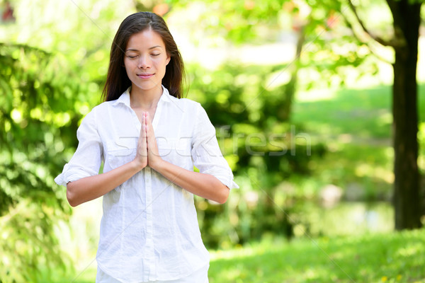Woman With Hands Clasped Meditating In Park Stock photo © Maridav