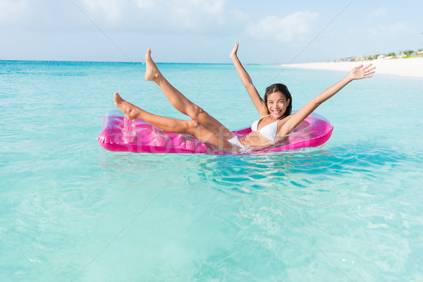 Beach fun girl playful on ocean float mattress Stock photo © Maridav