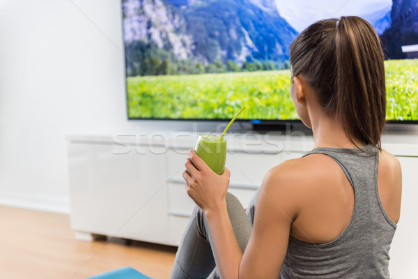 Maison femme potable smoothie vert regarder tv Photo stock © Maridav