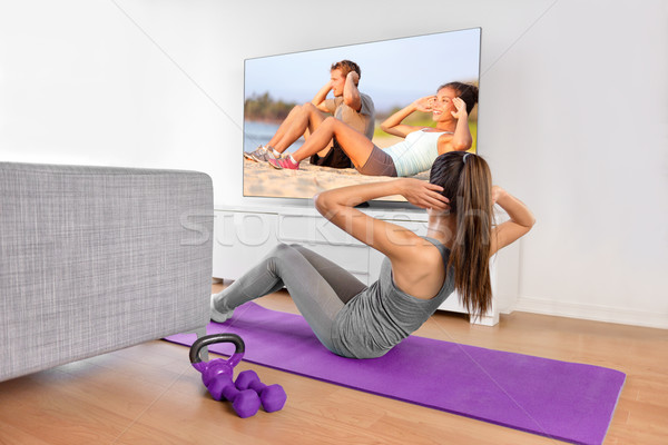 Stock photo: Home workout - woman exercising in front of TV