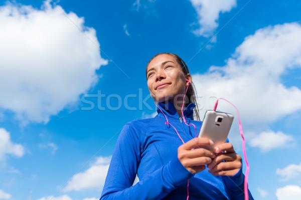 Running girl listening to music on smart phone Stock photo © Maridav