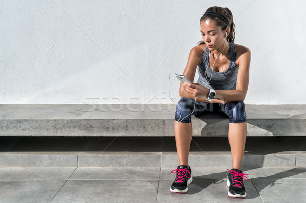 Fitness runner girl using music mobile phone app Stock photo © Maridav