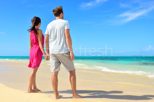 Stock photo: Beach couple looking at ocean view from behind