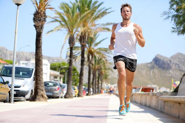 Fit male runner running outside on boardwalk Stock photo © Maridav