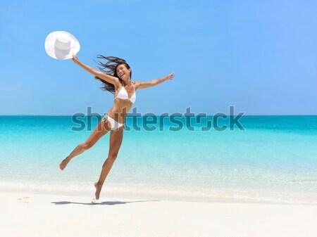 Happy carefree girl jumping on fun beach vacation Stock photo © Maridav