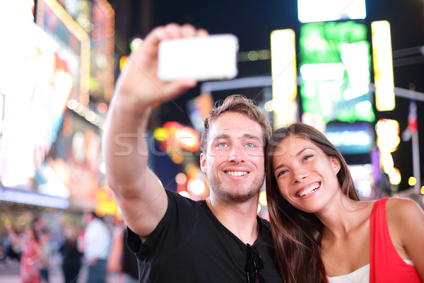Dating young couple happy in love taking selfie photo on Times Square, New York City at night. Beaut Stock photo © Maridav