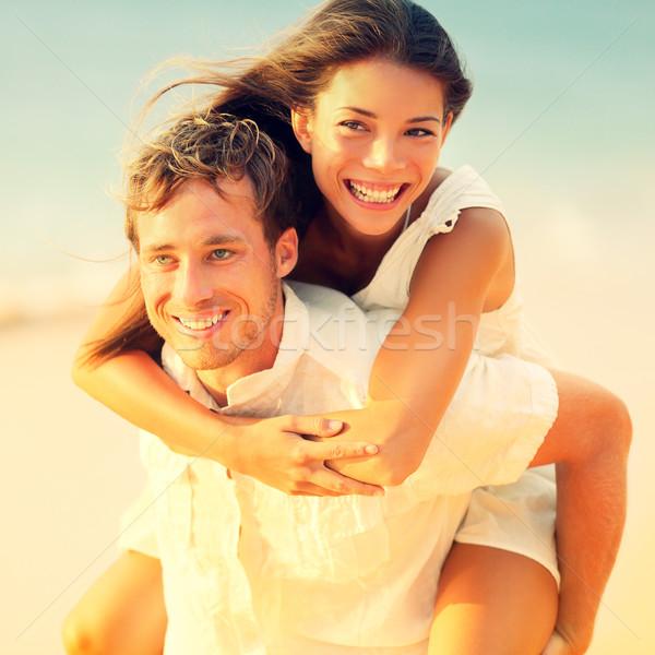 Romantic couple having fun piggyback on beach Stock photo © Maridav