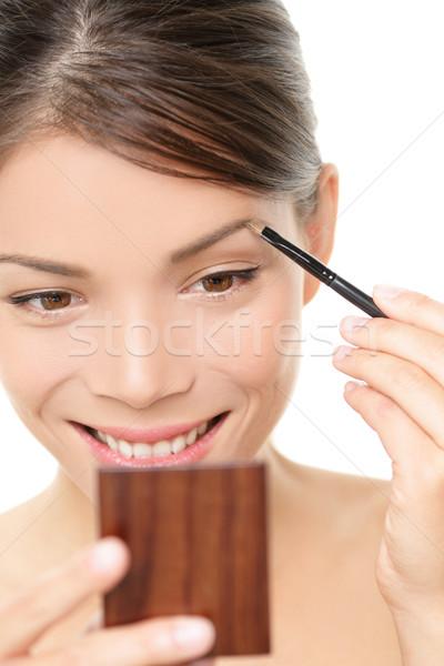 Makeup girl putting eyebrow color in mirror Stock photo © Maridav