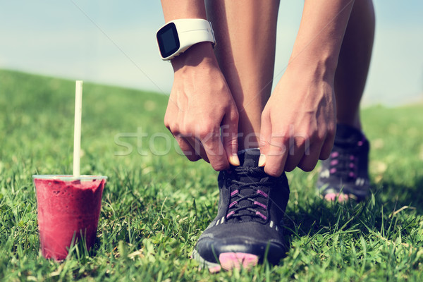 Weight loss - runner tying laces with smoothie Stock photo © Maridav