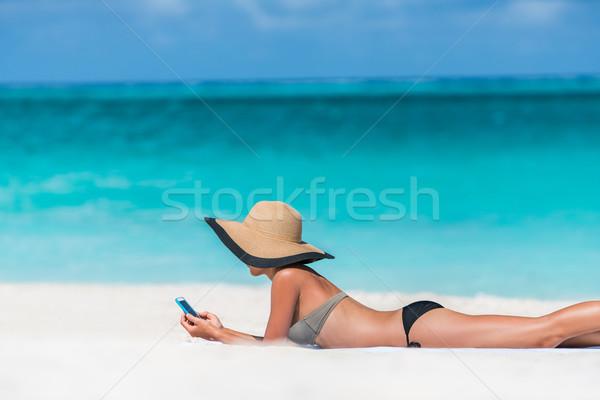 Beach vacation woman texting sms using phone app Stock photo © Maridav