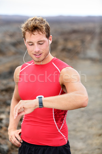 Running man looking at heart rate monitor stock photo © Maridav