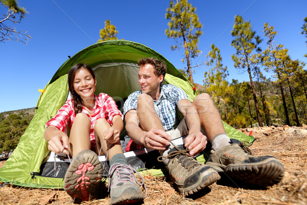 Stock photo: Camping people putting on hiking shoes by tent