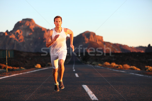 Athlete running sprinting at sunset on road Stock photo © Maridav