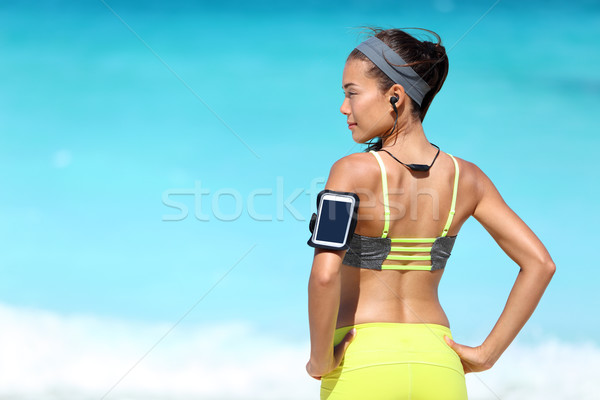 Fitness runner woman with fit back wearing phone armband and wireless headphones Stock photo © Maridav
