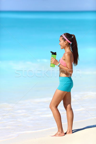 Beach runner taking running break drinking water Stock photo © Maridav