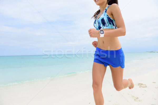 Runner running wearing smartwatch on beach Stock photo © Maridav