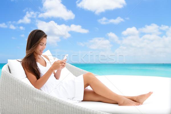 Smartphone woman using phone app on beach bed sofa Stock photo © Maridav