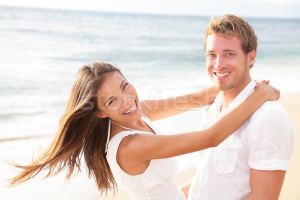 Happy couple on beach in love having fun Stock photo © Maridav