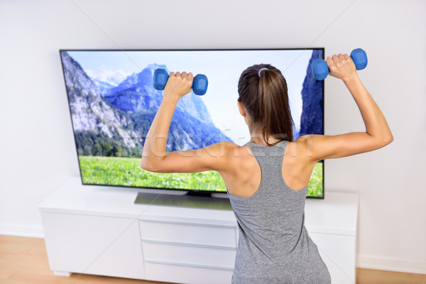 Fitness at home - woman working out in front of TV Stock photo © Maridav