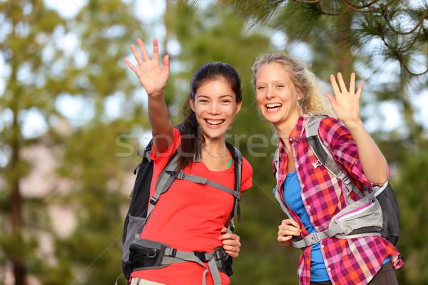 Hiking women waving hello smiling at camera happy Stock photo © Maridav