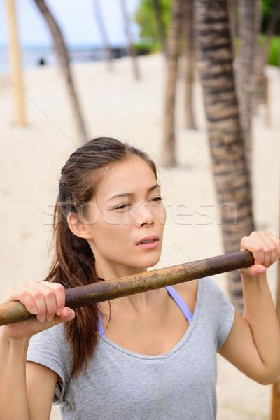 Exercise woman training arms on pull-up bar Stock photo © Maridav