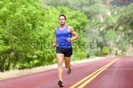 Running sprinting athlete man on road training Stock photo © Maridav