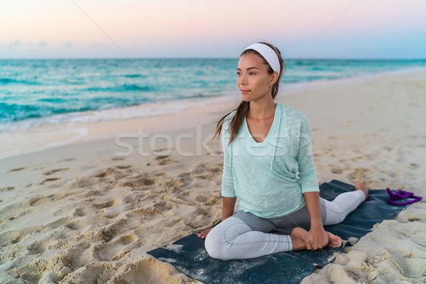 Yoga woman stretching leg with pigeon pose stretch Stock photo © Maridav
