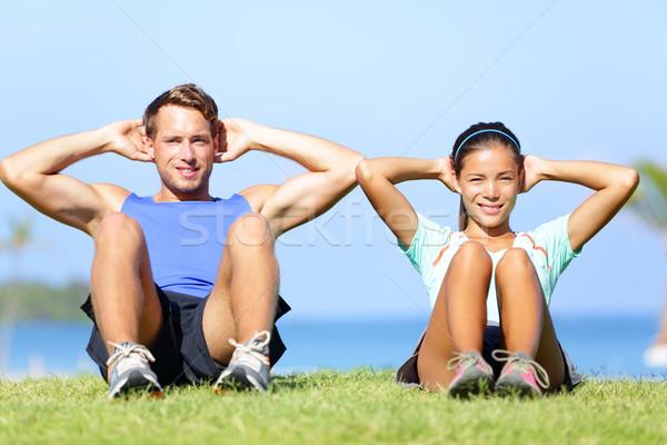 Sit ups - fitness couple exercising sit up outside Stock photo © Maridav
