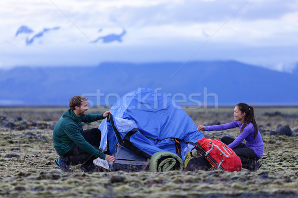 Tent - people pitching tent on Iceland at dusk Stock photo © Maridav