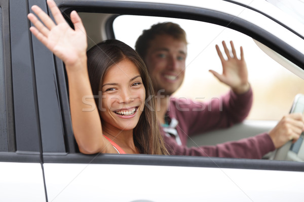 Drivers driving in car waving happy at camera Stock photo © Maridav