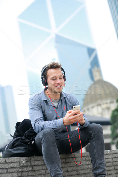 Városi férfi okostelefon visel fejhallgató zenét hallgat Stock fotó © Maridav