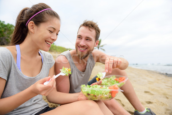 Happy young people eating healthy salad for lunch Stock photo © Maridav