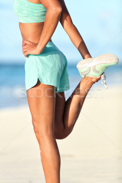 Female runner doing standing quadricep stretch running stretching exercise Stock photo © Maridav