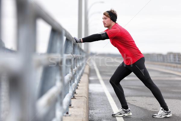 Man athlete stretching legs in winter outdoor run Stock photo © Maridav