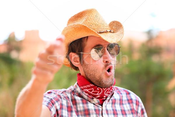Cowboy man with sunglasses and hat pointing Stock photo © Maridav