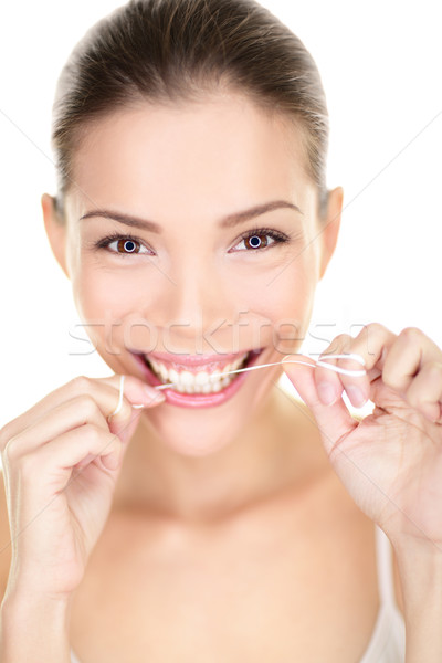 Woman flossing teeth smiling using dental flush Stock photo © Maridav
