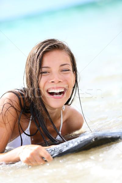 Surfboard laughing woman ashore - playful, wet Stock photo © Maridav