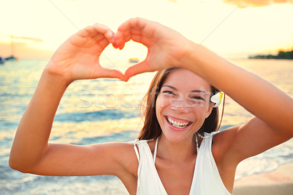 Stock photo: Love vacation - woman showing heart on beach
