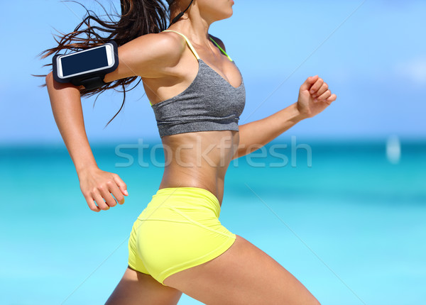 Fitness woman running fast wearing phone armband Stock photo © Maridav
