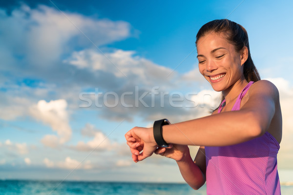 Active Asian girl using fitness tracker smart watch Stock photo © Maridav